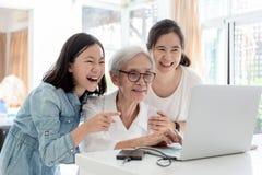 Moder och dotter som surfar internet; hålla ögonen på något intressera med farmodern, lycklig le asiatisk hög kvinnastund royaltyfri bild