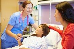 Moder och dotter som talar till den kvinnliga sjuksköterskan In Hospital Room Arkivfoto