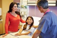 Moder och dotter som talar till konsulenten In Hospital Room Royaltyfri Foto