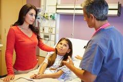 Moder och dotter som talar till konsulenten In Hospital Room Royaltyfri Fotografi