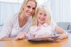 Moder och dotter som tillsammans använder minnestavlaPC Arkivbild