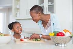 Moder och dotter som tillsammans gör en sallad arkivbild