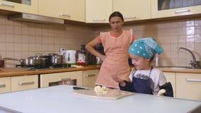 Moder och dotter som tillsammans hemma bakar i köket stock video