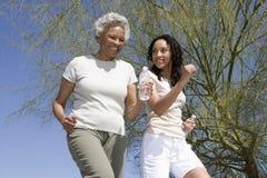 Moder och dotter som tillsammans joggar arkivfoto