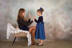 Moder och dotter som tillsammans kopplar av i stol Arkivfoto