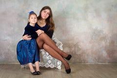 Moder och dotter som tillsammans kopplar av i stol Royaltyfri Bild