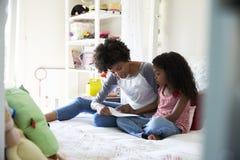 Moder och dotter som tillsammans placerar på sängläseboken Royaltyfri Foto