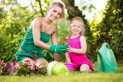 Moder och dotter som tillsammans planterar blommor royaltyfri foto