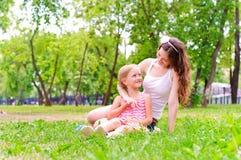 Moder och dotter som tillsammans sitter på gräset fotografering för bildbyråer