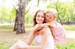 Moder och dotter som tillsammans sitter på gräset royaltyfri bild