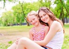 Moder och dotter som tillsammans sitter på gräset arkivfoto