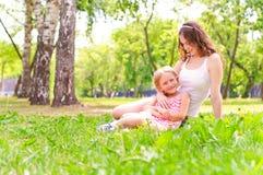 Moder och dotter som tillsammans sitter på gräset arkivbilder