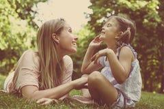 Moder och dotter som tillsammans sitter på grönt gräs Moder och arkivbild