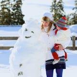 Moder och dotter som tillsammans spelar på solig vinterdag Arkivfoton