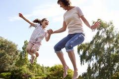 Moder och dotter som tillsammans studsar på trampolinen Arkivbild