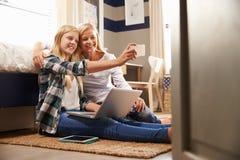 Moder och dotter som tillsammans tar selfie hemma Arkivbilder