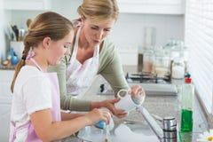 Moder och dotter som tillsammans tvättar sig upp royaltyfri bild