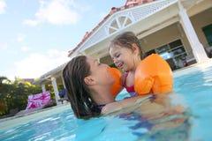 Moder och dotter som tillsammans tycker om i simbassängen Arkivfoton
