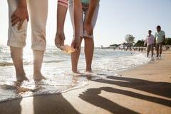 Moder och dotter som upp väljer ett skal på stranden Arkivbilder