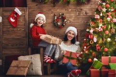 Moder och dotter som utbyter gåvor Fotografering för Bildbyråer