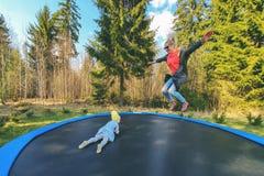 Moder och dotter som utomhus hoppar på trampolinen arkivbilder