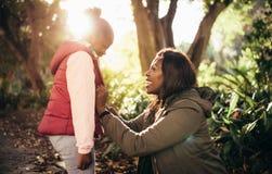 Moder och dotter som utomhus ler arkivbild