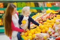Moder och dotter som väljer en apelsin Arkivfoto