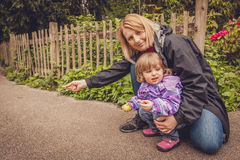 Moder och dotter som väntar för att mata ekorren Fotografering för Bildbyråer