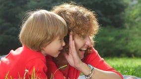 Moder och dotter som viskar skvaller på gräset lager videofilmer