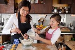 Moder och dotter tillsammans i kök royaltyfria bilder