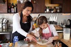 Moder och dotter tillsammans i kök Arkivbild