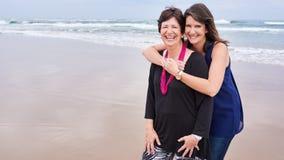 Moder och dotter tillsammans på stranden med kopieringsutrymme Arkivbild