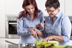 Moder och dotter under matlagning royaltyfri bild