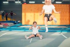 Moder- och dotterbanhoppning på trampolinen och görasplittring royaltyfri bild