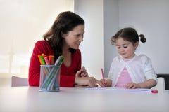 Moder- och dotterbarnet drar och målar tillsammans royaltyfria foton