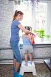 Moder- och dotterfamilj som bevattnar blommor på fönstret royaltyfria foton