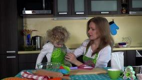 Moder- och dotterflicka med samma förkläden som förbereder sig för att laga mat stock video