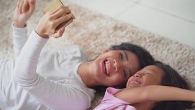 Moder- och dotterhållmobiltelefon på matta arkivfilmer