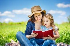 Moder- och dotterläsebok på grön sommaräng royaltyfri foto