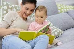 Moder- och dotterläsning behandla som ett barn boken Royaltyfria Foton