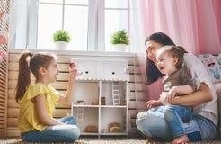Moder- och dotterlek med dockhuset arkivbilder