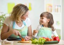 Moder- och dottermatlagning och bitande grönsaker Royaltyfri Fotografi