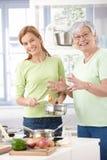 Moder- och dottermatlagning som ler tillsammans royaltyfri foto