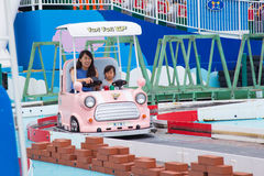 Moder- och dotterridningbil på den Tokyo kupolen fotografering för bildbyråer