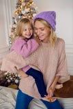 Moder- och dottersammanträde på den stora sängen Royaltyfria Bilder