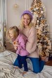Moder- och dottersammanträde på den stora sängen Fotografering för Bildbyråer