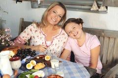 Moder- och dottersammanträde på en tabell för ett hurtigt mellanmål arkivfoto