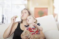 Moder- och dottersammanträde på soffan och att blåsa bubblar i vardagsrummet Royaltyfri Bild