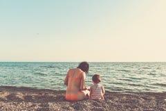 Moder- och dottersammanträde på stranden Royaltyfri Fotografi
