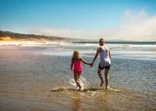 Moder- och dotterspring i vågorna på stranden Royaltyfri Bild